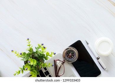 Flat lay of business accessories on desk, mobile, laptop, pen, coffee cup, glasses, compass and plant pot.