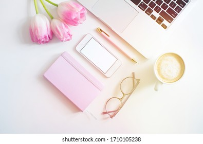 Flat lay business female workplace with mockup smartphone, keyboard laptop, coffee, and pink tulips. White colors. Minimalism. Home office. Top view. Copy space for text
