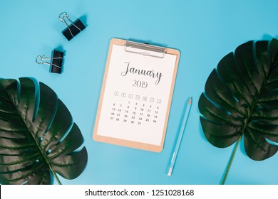 Flat lay calendar with clipboard, palm leaves and pencil on blue background. January 2019. top view.