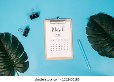 Flat lay calendar with clipboard, palm leaves and pencil on blue background. March 2019. top view.
