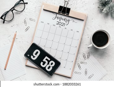 The flat lay of a calendar diary, flip clock screensaver on the phone, mug, glasses, clips, and pencil, the concept of a fresh start in the New Year