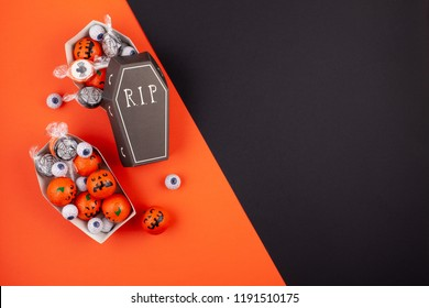 Flat lay of candies and chocolates in the coffins as halloween treats, accessory decoration Happy Halloween festival background concept.