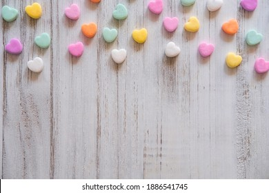 Flat lay Candy Hearts Pattern - Pastel rainbow conversation heart candy design for Valentine's Day. Top view sweet decor for Easter.
