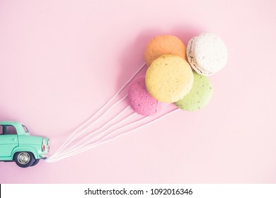 Flat lay of car model with colorful macaroons in form of balloons. Just married creative minimal concept.