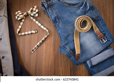 Flat lay of casual suit, blue jeans, wicker belt and checkered bowtie on brown wooden background. Top view.