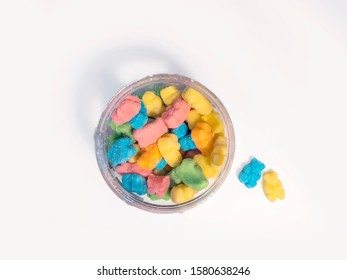 Flat lay of CBD infused medicinal sour candy gummies used for healing on a plain white background