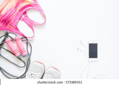 Flat lay of cellphone, pink sport bra, jump rope and sneaker on white background, Working out and healthy concept, top view