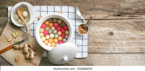 "Flat lay Chinese food ""tang yuan"" glutinous rice ball sweet hot soup on rustic wooden kitchen table top."