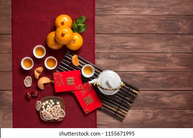 Flat lay Chinese new year food and drink on wooden table top. Texts appear in image: Prosperity, Spring. Text space image.