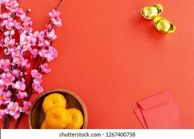 Flat lay Chinese New Year Background - Cherry Blossom, Mandarin Orange, Red Envelop and Golden Ingots on red background. Translation text on Ingot - Prosperity.