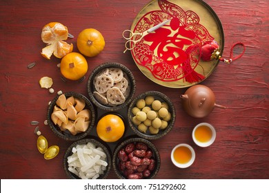 Flat lay Chinese new year food and drink on rustic red wooden table top. Text appear in image: Prosperity.