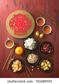 Flat lay Chinese new year food and drink still life on rustic wooden background. Translation of text paper in image: Prosperity, Wealthy.