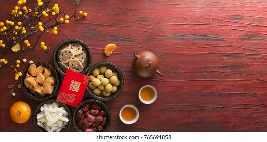 Flat lay Chinese new year food and drink still life on rustic wooden background. Translation of text appear in image: Prosperity.