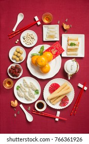 Flat lay Chinese new year food and drink, reunion dinner food still life on red table top background. Translations of text appear in image: Prosperity.