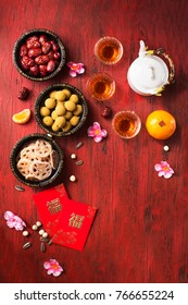 Flat lay Chinese new year food and drink still life on red wooden rustic background. Translation of texts appear image: Prosperity and Wealth.