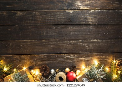 Flat lay Christmas background. Christmas decoration and christmas lights on dark wooden background with copy space top view