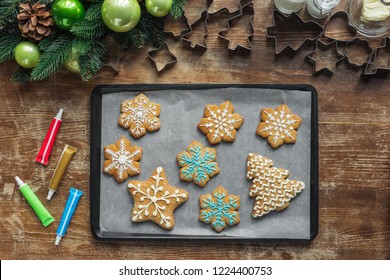 flat lay with christmas cookies on baking pan, christmas wreath and cookie cuttrers on wooden surface