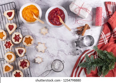 Flat lay with christmas cookies on marble surface with christmas decorative pine branch, jam, gift and cookie cutters