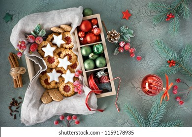 Flat lay with Christmas cookies and seasonal decorations in wooden box on gray rustic background with fir twigs and cinnamon sticks