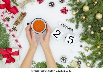 Flat lay of Christmas decoration ornaments on white background and woman hand holding cup of tea - Trendy minimal flat lay design. 25 dec perpetual calendar.