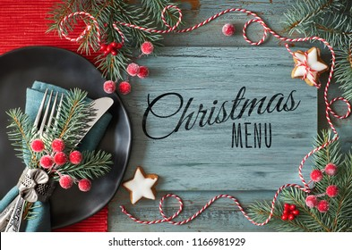 """Flat lay with Christmas decorations in green and red with frosted berries and trinkets and black plate with crockery, text """"Christmas menu"""""""