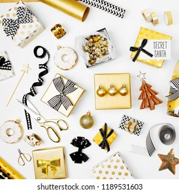 Flat Lay Christmas or Party Background with Gift boxs, Champagne bottle, Bows, Decorations and Wrapping Paper in Gold and Black colors. Flat lay, top view