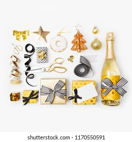 Flat Lay Christmas set with Gift boxs, Champagne bottle, Bows, Decorations and Wrapping Paper in Gold and Black colors. Flat lay, top view
