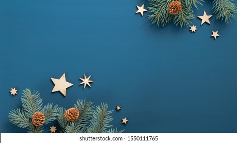Flat lay Christmas tree branches with cones and wooden vintage stars over blue background. Top view. Xmas banner mockup with copy space, greeting card template.