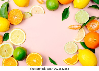 Flat lay of citrus fruits like lime, lemon, orange and tangerine with orange tree leaves on light pink background making a frame