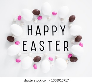 Flat lay close up of happy Easter text, eggs and sweets over white background