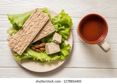 Flat lay. Close up, still life. Dietary vegan snack consisting of green salad, a piece of tofu soy cheese, a handful of almonds, yeast free bread, a cup of tomato juice. White wooden background.