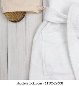 Flat lay closeup of a bathrobe with a scrub brush a on a white wooden surface. Bath and Spa Concept