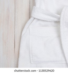 b053811288 Flat lay closeup of a white terry cloth bathrobe on a rustic white wooden  surface.