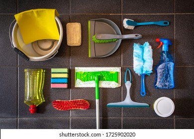 Flat lay with collection of cleaning materials on a black tile background