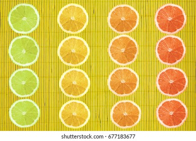Flat lay of colorful citrus slices on yellow bamboo texture background, perfectionism