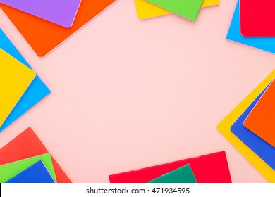 Flat lay colorfull notebooks on bright pink background around copy space. Back to school.
