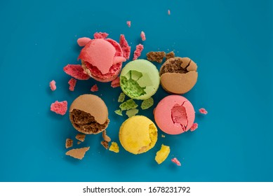 Flat lay of colourful smashed macarons with lots of crumbles around on the blue background. Failure holiday concept