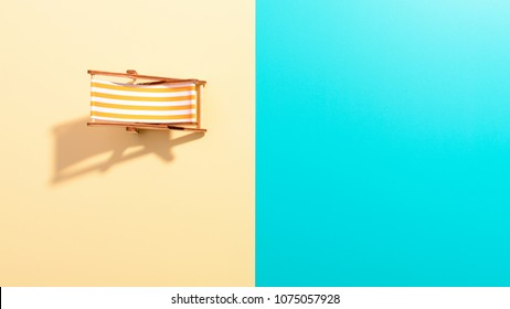 Flat lay of a composed miniature of beach lounge area with deck chair on the colorful surface
