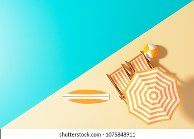 Flat lay of composed miniature of beach lounge area with umbrella and sunbeds on colorful surface.