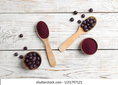 Flat lay composition with acai powder and fresh berries on wooden background