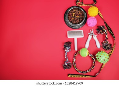 Flat lay composition with accessories for dog and cat, toys, dry food, dog biscuits, cookies, brushes, hairbrushes, balls, collar on red background. Pet food. Copy space.