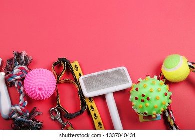 Flat lay composition with accessories for dog and cat, toys, dry food, dog biscuits, cookies, brushes, balls, collar on red background.