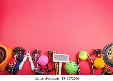 Flat lay composition with accessories for dog and cat, toys, dry food, dog biscuits, cookies, brushes, balls, collar on red background.  Copy space.