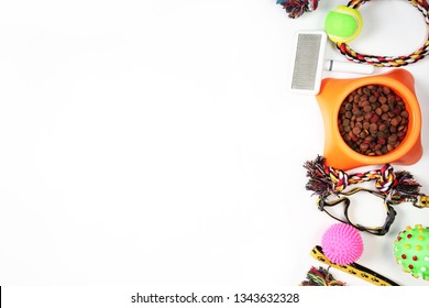 Flat lay composition with accessories for dog and cat, toys, dry pet food, dog biscuits, cookies, brushes, hairbrushes, balls, collar on white background. Copy space.