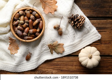 Flat lay composition with acorns, pumpkin and white knitted fabric on wooden table