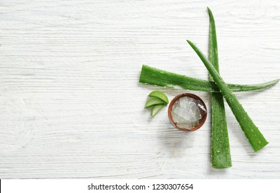 Flat lay composition with aloe vera leaves on wooden background. Space for text