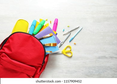 Flat lay composition with backpack, school stationery and space for text on light background