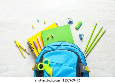 Flat lay composition with backpack and school stationery on light background
