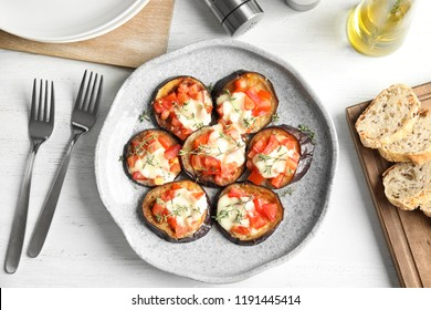 Flat lay composition with baked eggplant, tomatoes and cheese on table