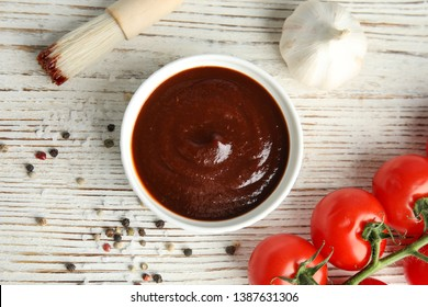 Flat lay composition with barbecue sauce on white wooden table